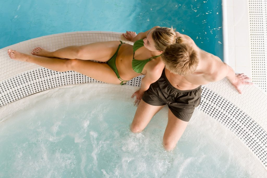 Young couple relaxing by hot tub and pool