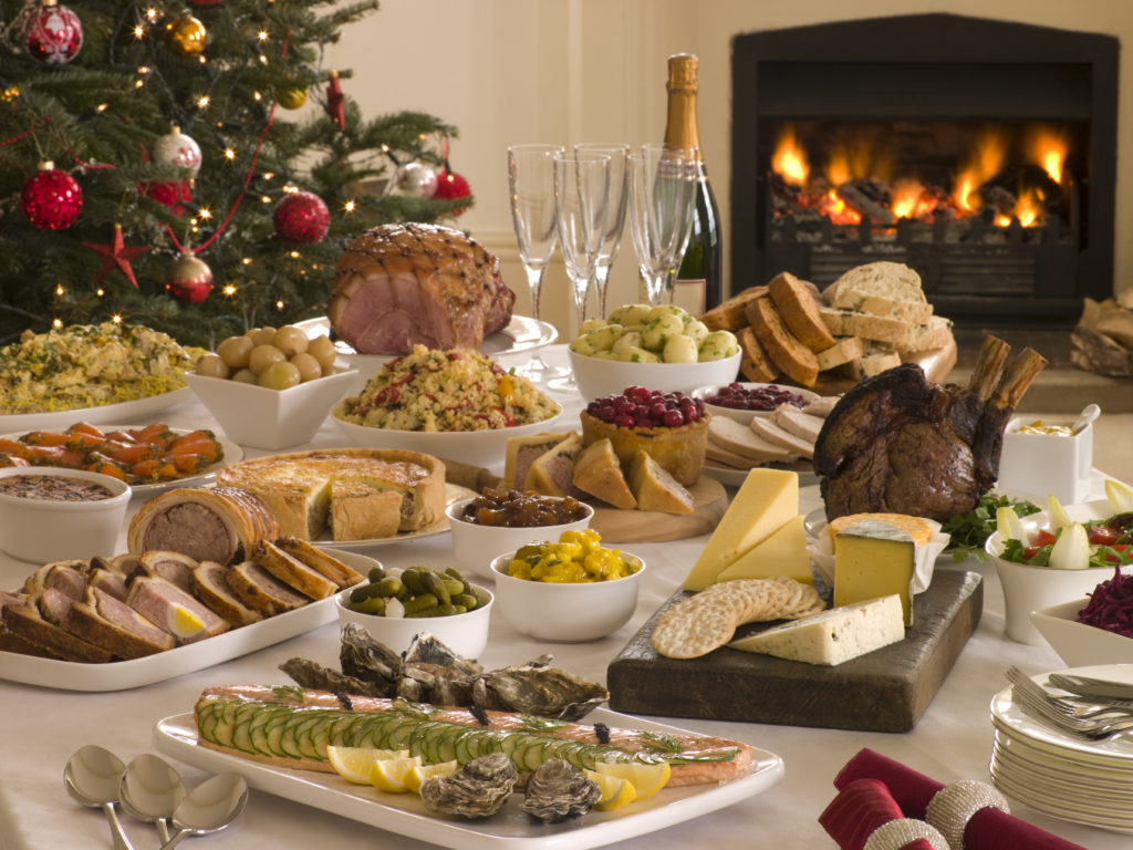 a-large-christmas-dinner-spread-out-on-a-table-with-a-log-fire-in-the-background